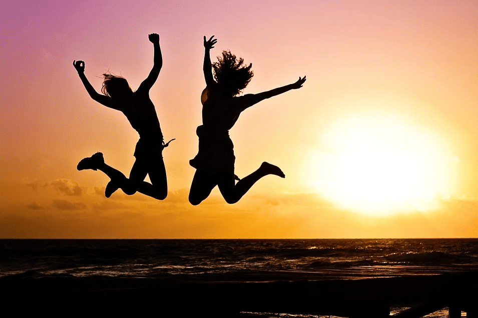 silhouette of two women jumping