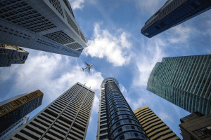 airplane flying above the skyscrapers