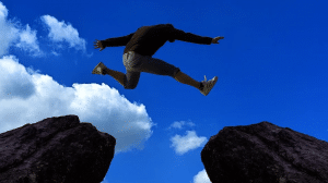 man jumping from one cliff to another