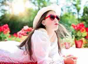 pretty woman wearing red sunglasses and a white hat